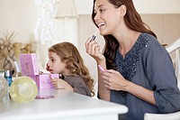 Young woman and little girl applying make-up at dressing table (thumbnail)