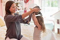 Happy woman dressing her daughter at home (thumbnail)