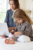 Girl looking at a smart phone with her mother working on a laptop on the bed