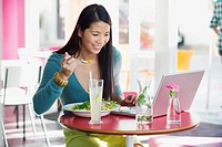 Beautiful woman eating food while looking at laptop in a restaurant