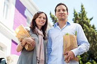 Portrait of a couple standing with paper bags full of vegetables