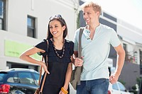 Smiling young couple standing on a street (thumbnail)