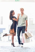 Young couple standing together with shopping bags