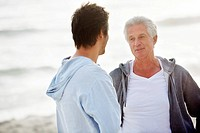 Senior man talking to his son on the beach