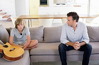 Father complaining to teenage boy sitting with a guitar at home