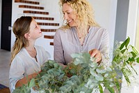 Mid adult woman and her daughter touching leaves and smiling
