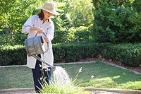 Senior woman in straw hat watering plants in a garden