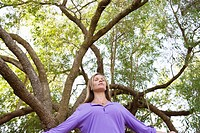 Young woman standing under a tree with her eyes closed