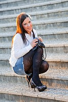 Attractive young woman is squatting on staircase and smiling with a purse in hand