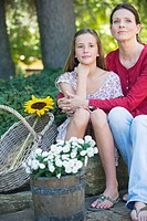 Little girl and mother sitting outdoors with flowers in the basket (thumbnail)