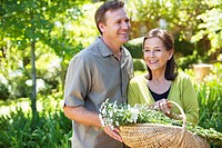 Man with his mother holding basket of flowers outdoors