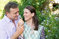 Happy mature couple smelling flowers in the garden