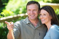 Smiling man showing something to his wife outdoors