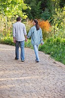 Rear view of a mature couple walking in a garden
