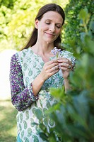 Smiling mature woman looking at flowers in garden