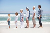 Family standing in row along the beach with kids