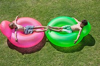 Two boys relaxing on inflatable rings (thumbnail)