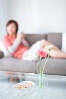 Woman lying on sofa with coffee cup