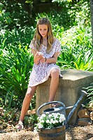 Cute little girl text messaging while sitting in garden