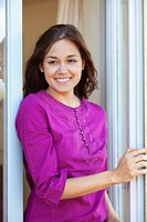 Woman standing at a window and smiling