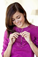 Beautiful young woman looking at golden locket and smiling