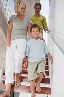Couple with their son moving down from a staircase