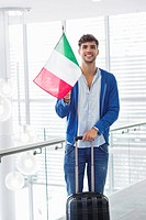 Portrait of a man holding Italian flag and a suitcase at an airport