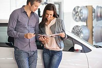 Couple looking at car catalog in showroom
