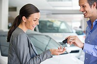 Happy salesperson handing car key to a woman in a showroom