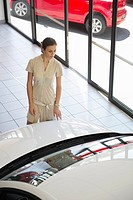 Young woman looking at a car in a showroom
