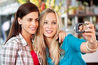 Female friends taking a picture of themselves with a camera