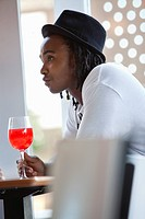 Young man having red wine at a bar