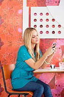 Young woman sitting in a cafe and text messaging on a mobile phone