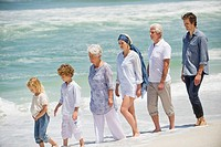 Multi generation family walking in a line on the beach
