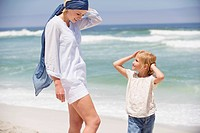 Woman with her daughter standing on the beach
