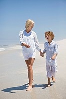 Woman walking on the beach with her son