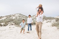 Man walking on sand with their children