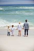 Couple with their children standing on the beach