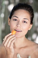 Portrait of a young woman eating a carrot