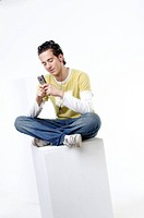 Young man with his eyes closed using a mobile phone
