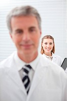 Smiling woman in lab coat with man in foreground