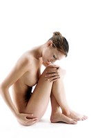 Side profile of a naked young woman sitting on the floor with her hand on her knee