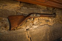 Replica of an old circa 1790 musket displayed above a stone fireplace in an old circa 1760 home, Lanaudiere, Quebec, Canada
