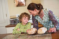 Cute little boy and mother baking bread in kitchen