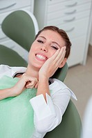 Woman having toothaches in dentist´s chair