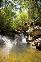 Composite image multiple shots of a young man jumping from a rock into a swimming hole at Skinny Dip Falls, North Carolina