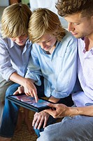 Man and two little boy looking at digital tablet