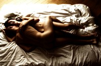 High angle view of a young couple lying naked in bed embracing each other