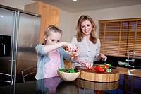 Mother and daughter preparing healthy meal in kitchen