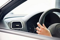 Close_up of a human hand on car steering wheel
